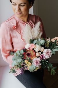 Kaboompics - A woman with a bouquet wrapped in paper