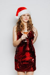 Kaboompics - Woman in Red Dress and Santa Hat holding a glass of wine on a white Background