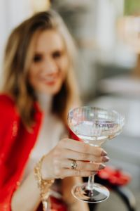 Kaboompics - Woman in a red jacket holds a glass