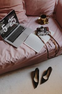 Kaboompics - Workplace with a laptop, organizer, high heels, old camera shoes and coffee on a pink couch