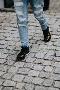 Woman in black sneakers and blue jeans