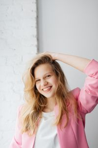 Kaboompics - Beautiful teenage girl with long blonde hair wearing a pink jacket