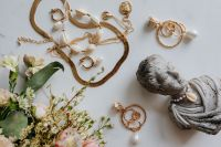 Gold jewellery in white marble - flowers and a small sculpture, a shell