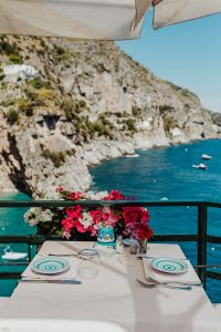 Kaboompics - Restaurant tables by the sea, petunia flowers