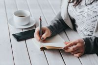 Coffee on table with a woman writing