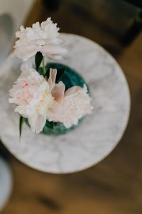 Peony flowers in vase on marble table