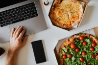 Kaboompics - Top view of the desk with pizza, laptop, phone and hands