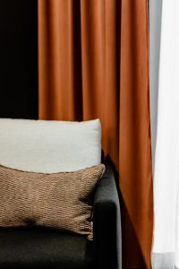 Kaboompics - Grey armchair and pillow - orange curtain