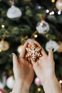 Woman holds a gingerbread cookie, Christmas tree background