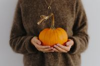 Kaboompics - Women's hands in sweater are holding pumpkin