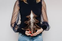 Kaboompics - Woman in Black Blouse Holds a Christmas Tree Bauble