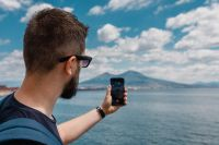 A man taking a picture of the volcano Vesuvius with his mobile phone, Naples, Italy