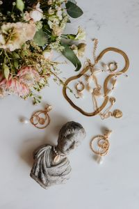 Kaboompics - Gold jewellery in white marble - flowers and a small sculpture, a shell