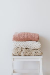 Kaboompics - Colourful sweaters on the wooden stool
