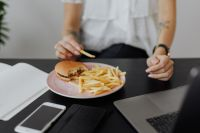 Businesswoman eats at work hamburger and fries