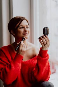 Kaboompics - A woman in a red sweater does her make-up - applies a foundation with a brush