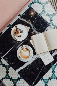 Book coffee and cake with meringue and whipped cream on black marble
