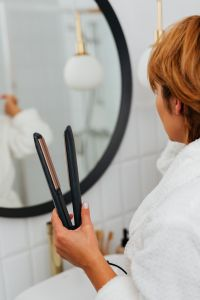 Kaboompics - Woman Straightening Healthy Hair With Flat Iron - Hair Straightener