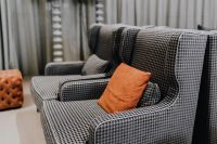 Cozy grey armchairs with orange pillow in living room