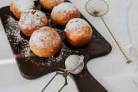 Homemade doughnuts covered with powdered sugar. Traditional speciality on Fat Thursday in Poland.