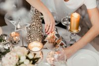 A woman decorates a Christmas table with silver decorations and white porcelain tableware