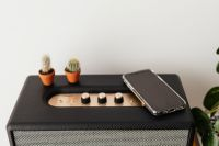 Kaboompics - Black speaker on marble table, white wall, mobile phone, cacstus
