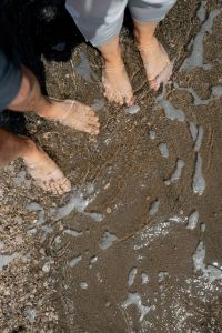 Kaboompics - Legs of young couple standing together at the sand in the water at sea beach