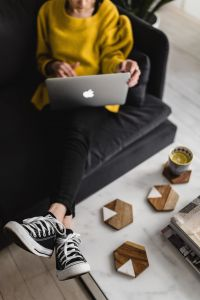 Kaboompics - Woman with legs on the coffee table, wearing converse sneakers and working on her laptop