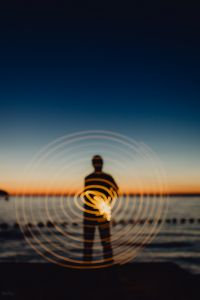 Kaboompics - Light painting. The man waving fairy lights at the sea at sunset.