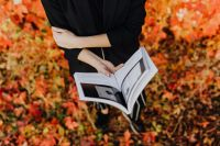Girl with the Grafconf book on the background of coloured leaves