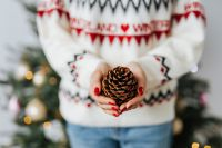 Kaboompics - Woman in a white Christmas sweater holds a cone