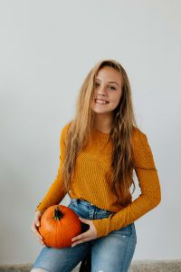 Kaboompics - A young girl holds a pumpkin in her hand