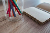 Kaboompics - Small notebooks with colourful pencils in a jar on a wooden desk
