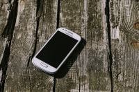 Kaboompics - White smartphone on a wooden background