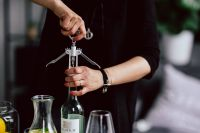 Kaboompics - Hands opening wine bottle with corkscrew