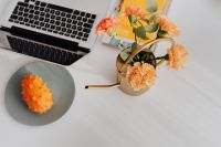 Kaboompics - MacBook laptop & orange Dianthus (carnation or clove pink) flowers on desk, kiwano fruit