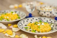 Yellow rice with greens on a cute plate with blue hearts and a table decorated with flower petals