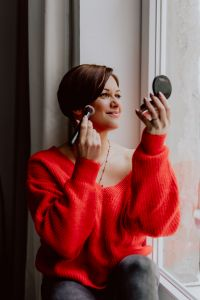 A woman in a red sweater does her make-up - applies a foundation with a brush