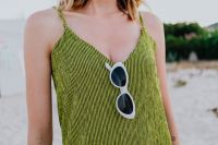 Kaboompics - A woman in a green dress on the beach with white sunglasses