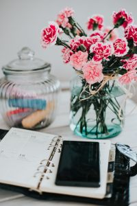 Organizer, mobile phone and lovely pink flowers