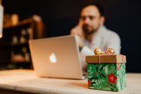Designer sits at a desk with a small Christmas gift
