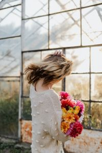 A woman with beautiful colorful dahlia flowers
