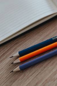 Kaboompics - Notebooks with colourful pencils on a wooden desk