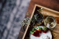 Strawberries with cream and glass of white wine on wooden tray