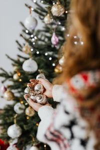 Kaboompics - Woman in a white Christmas sweater holds bunch of baubles