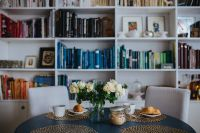Round breakfast table with white flowers by the bookcase
