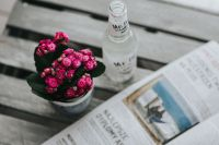 Little pink flowers with a bottle of water and a magazine