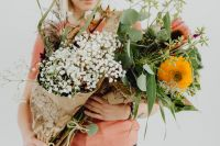 Kaboompics - A woman holds many different flowers and leaves in her arms