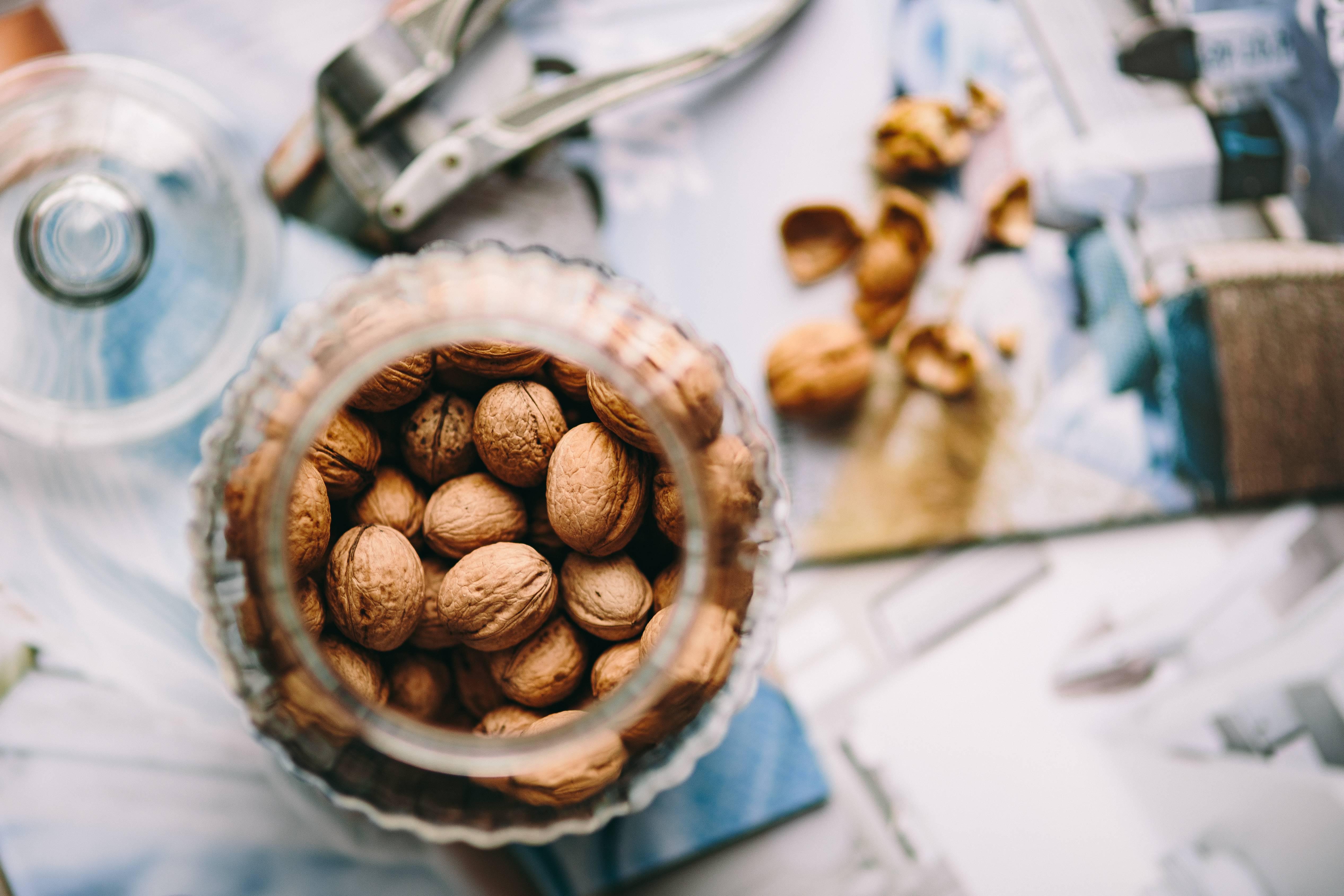 Glass jar full of walnuts and a nutcracker